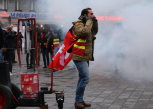 Un manifestant de la CGT se bouche les oreilles avant une explosion de pétard lors de la manifestation contre la réforme des retraites du 5 décembre 2019.