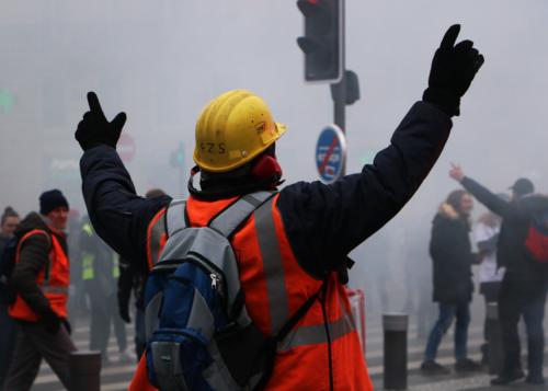 Un manifestant en tenue de travail lève les bras en signe de joie après l'explosion d'un pétard lors de la manifestation contre la réforme des retraites du 5 décembre 2019.