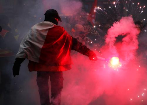 Un manifestant agite un fumigène de couleur rouge à la manifestation contre la réforme des retraites du 5 décembre 2019..