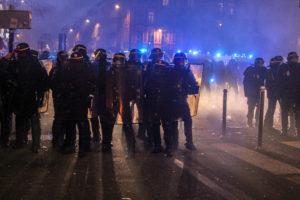 """Ces fameux """"hommes en noir"""", interdisant l'accès à la place de la République, éclairés par la lumière jaune des phares et la lumière bleue des gyrophares."""