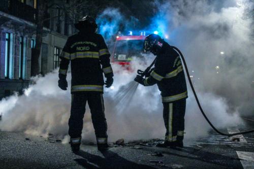 La lumière bleutée qui filtre à travers la fumée éclaire les deux hommes, venus à bout des flammes qui ravagaient la rue.