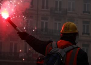 Manifestant en tenue de travail avec un fumigène lors de la manifestation contre la réforme des retraites du 5 décembre 2019.