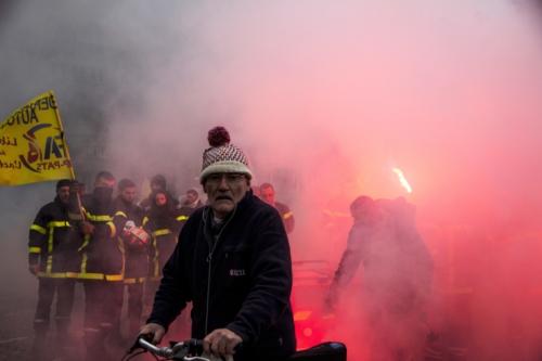 Au départ de la manifestation, un retraité traverse ébahi le cortège des pompiers en grève