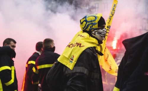 """Un manifestant avec un foulard """"tête de mort"""" traverse le cortège des pompiers en grève"""