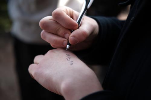 """Un militant recopie le numéro de la """"base arrière"""", qui lui apportera de l'aide en cas de garde à vue, sur sa main. Si l'opération prévue aujourd'hui ne s'annonce pas musclée, elle n'en reste pas moins illégale."""