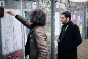 """Certaines affiches du collectif Décidez pour Lille ont été déteriorées. Julien Poix accuse, avec quasi-certitude, des partis adverses. Nicolas, son """"chauffeur"""" d'une matinée, profite de ce tour des bureaux de votes pour réparer les dégâts."""