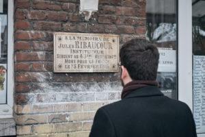 """Julien Poix, lorsqu'il n'est pas candidat insoumis, enseigne l'histoire/géographie au collège. Entre deux bureaux, il s'arrête quelques instants devant un plaque commémorative de la seconde guerre mondiale. """"Voilà le prof !"""", plaisante Nicolas."""