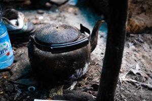Les réfugiés réchauffent leurs thés grâce au feu de bois.